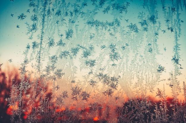 Struttura del ghiaccio congelato vintage modello gelido sulla finestra al tramonto fiocchi di neve congelati e brina sopra