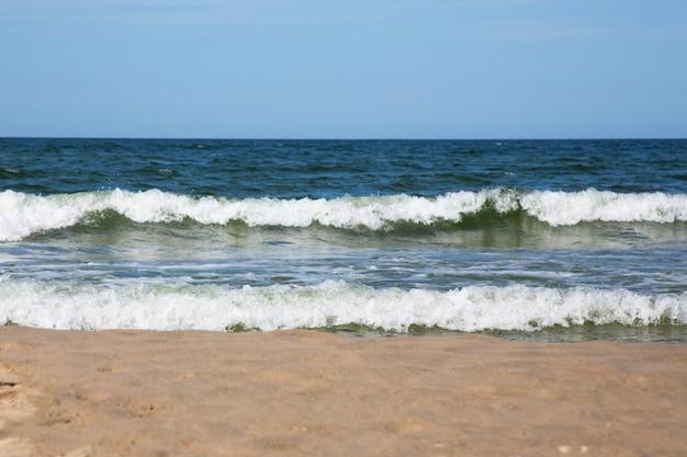 Onde bianche spumeggianti sulla spiaggia sabbiosa del mar baltico. mare blu e cielo blu brillante, alta marea. estate in spiaggia