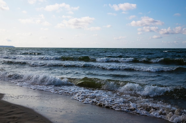 Onde bianche spumeggianti sulla spiaggia sabbiosa del mar baltico