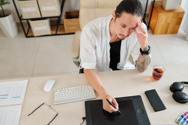 Designer accigliato che soffre di mancanza di ispirazione quando lavora al progetto per il cliente
