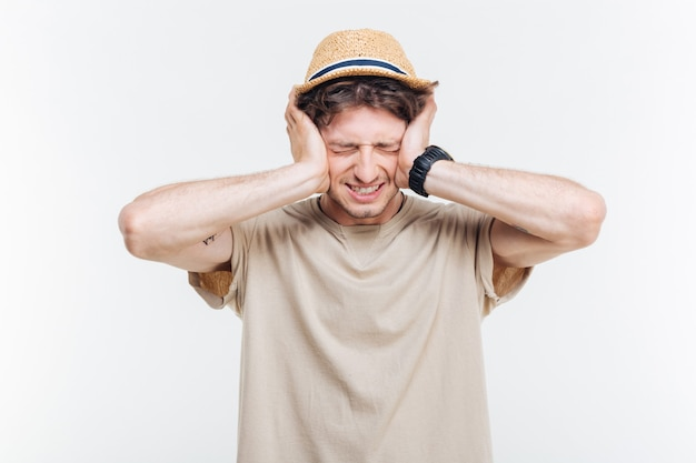 Accigliato bel giovane uomo coperto le orecchie con le mani su sfondo bianco