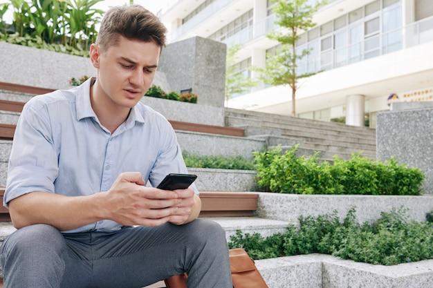 Accigliato giovane uomo d'affari infelice seduto sui gradini e rispondere ai messaggi di colleghi e clienti
