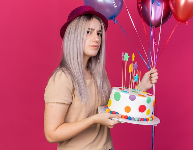 Accigliata giovane bella ragazza che indossa un cappello da festa che tiene palloncini con torta isolata sulla parete rosa