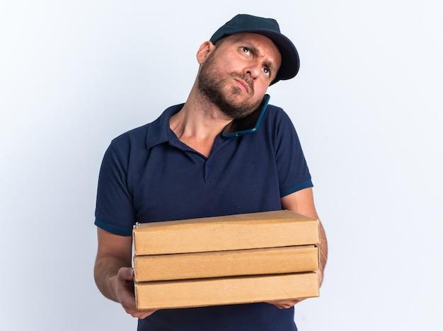 Accigliato giovane fattorino caucasico in uniforme blu e berretto che tiene i pacchetti di pizza parlando al telefono guardando in alto isolato sul muro bianco