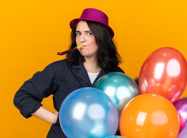Accigliata giovane donna caucasica del partito che indossa un cappello da festa che tiene un mazzo di palloncini guardando davanti tenendo la mano sulla vita che soffia il corno del partito isolato sul muro arancione