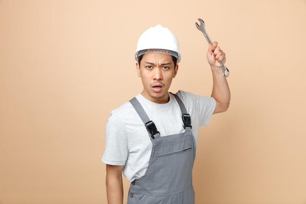 Accigliato giovane operaio edile che indossa il casco di sicurezza e chiave di sollevamento uniforme