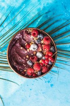 Frullato di acai congelato in guscio di noce di cocco con lamponi, banana, mirtilli, frutta e muesli su sfondo di cemento. colazione, pasto sano per le vibrazioni estive, vista dall'alto, spazio per il testo