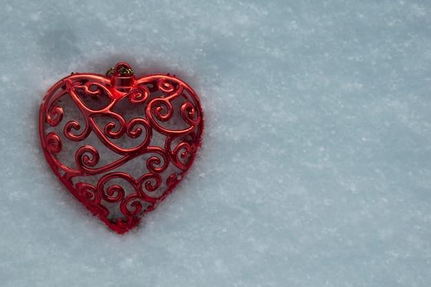 Bello cuore rosso congelato sulla neve. vista dall'alto