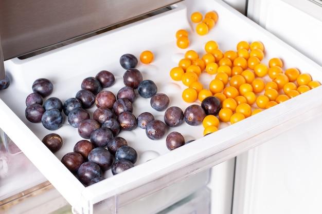 Bacche congelate nel congelatore. prugne surgelate, prugne ciliegie sul ripiano del congelatore.