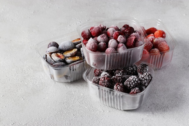 Bacche congelate come ciliegie, fragole, prugne e more nelle scatole di immagazzinaggio sullo sfondo grigio cemento