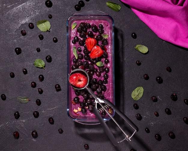 Sorbetto congelato ai frutti di bosco decorato con fragole su uno spazio nero.