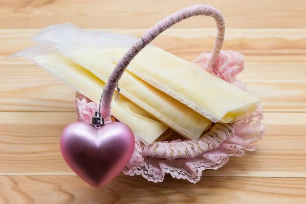 Latte materno congelato in sacchetti di stoccaggio sul cesto con cuore rosa su fondo di legno con spazio di copia per il testo. il miglior alimento nutrizionale per neonati. estrazione del latte materno per il brodo risparmiato