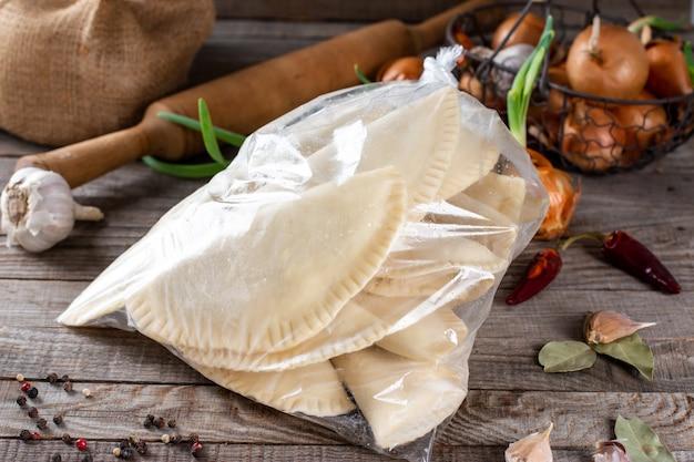 Chebureks congelati nella borsa su un tavolo in legno con ingredienti