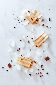 Gelato gelato al caffè congelato con chicchi di caffè su un bastone di legno su sfondo di marmo, vista dall'alto. sfondo delizioso estivo