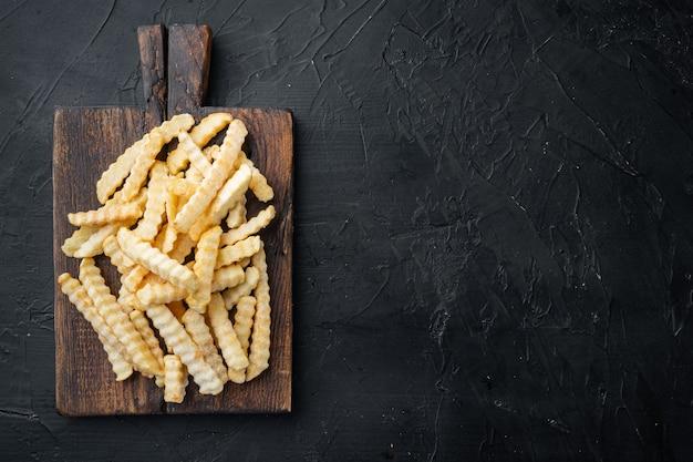 Patatine fritte congelate del forno della piega messe sul tagliere di legno