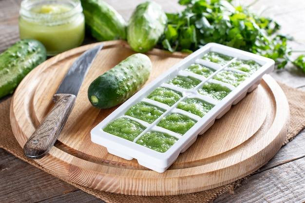 Purea di cetriolo congelata in vassoi per cubetti di ghiaccio pronti per il congelamento su un tagliere su un tavolo di legno. concetto di cibo congelato.