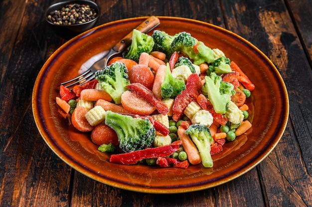 Verdure tagliate congelate, broccoli, peperoni, pomodori, carote, piselli e mais su un piatto. sfondo in legno scuro. vista dall'alto.