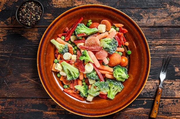 Verdure tagliate congelate, broccoli, peperoni, pomodori, carote, piselli e mais su un piatto