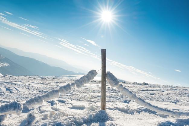 Recinto congelato con ghiaccio e neve nel villaggio alpino di inverno. paesaggio di montagna