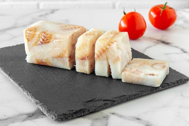 Filetto di pesce pangasio congelato su tavola di pietra pronto per la cottura.