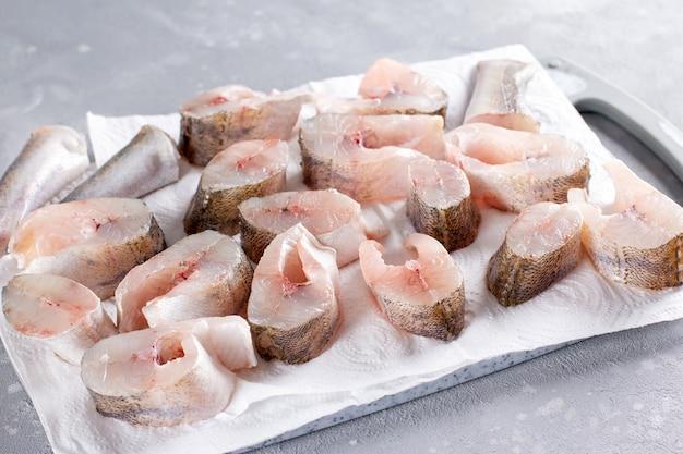 Pesce congelato su un tagliere su un tavolo luminoso. surgelato