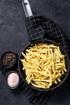 Patate fritte congelate in una padella. sfondo nero. vista dall'alto. spazio per il testo