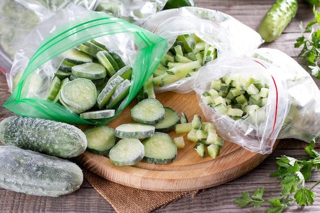Fette verdi fresche congelate del cetriolo su un tagliere sulla tavola di legno. concetto di cibo congelato