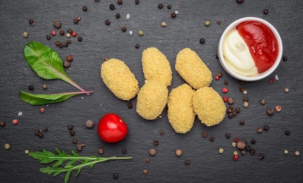 Congelato. mozzarella fritta, morsi di formaggio cheddar, palline con ketchup su tavola di pietra rustica