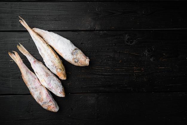 Set di pesce crudo congelato di capra, su sfondo di tavolo in legno nero, vista dall'alto piatta, con spazio di copia per il testo