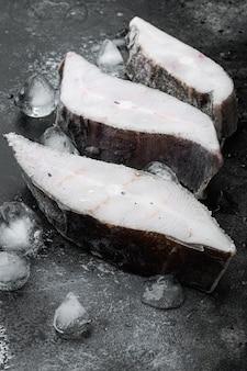 Set di bistecca di halibut congelato, su sfondo nero tavolo in pietra scura dark