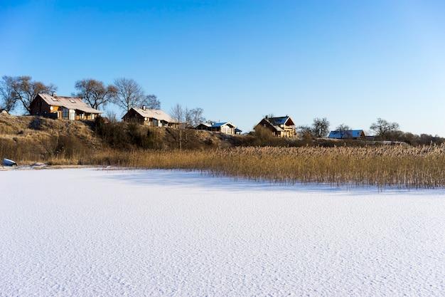 Lago ghiacciato, case e canne secche mattina gelida in inverno contro il sole