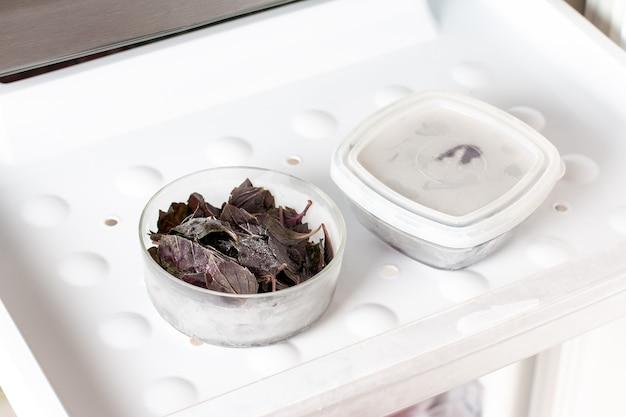 Foglie di basilico congelate nel congelatore. verdure surgelate. concetto di una sana alimentazione.