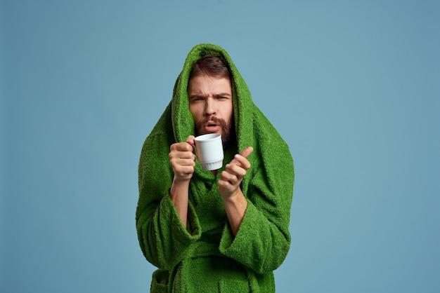 Uomo congelato in una calda veste con una tazza di bevanda calda su un blu