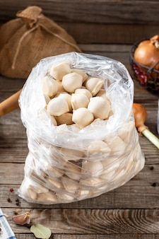 Gnocchi di carne congelati in un sacchetto di plastica su sfondo di legno