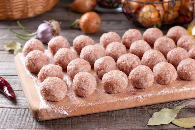 Le polpette congelate si trovano su una tavola di legno. i semilavorati di carne cruda sono pronti per la cottura, orizzontali