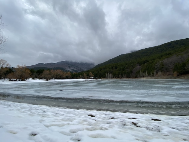 Lago di montagna ghiacciato coperto di ghiaccio sottile.