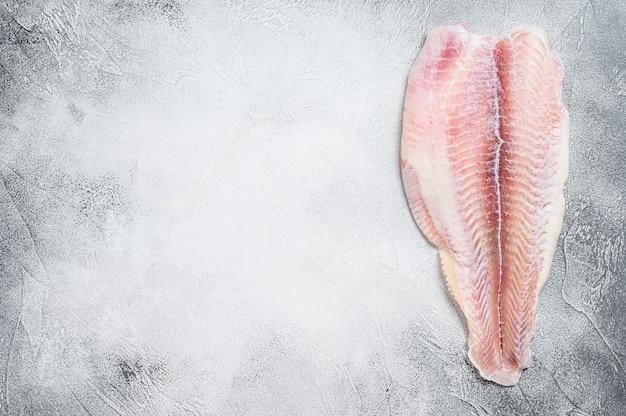 Filetto di pesce pangasio congelato. sfondo grigio. vista dall'alto. copia spazio.