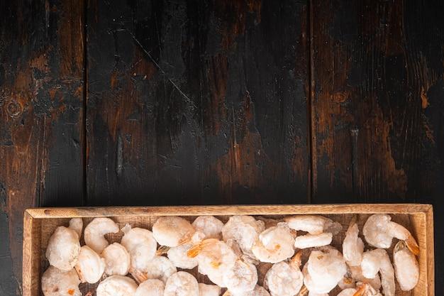 Set di gamberi bolliti sgusciati congelati, in scatola di legno, su un vecchio tavolo di legno scuro, vista dall'alto piatta
