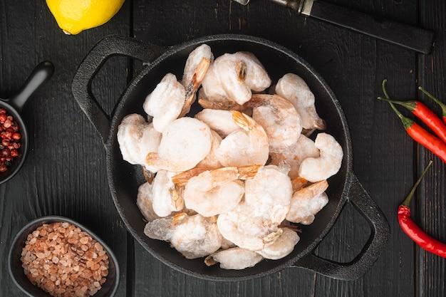 Gamberi bolliti sgusciati congelati impostati, in padella o pentola in ghisa, sul tavolo di legno nero, vista dall'alto laici piatta