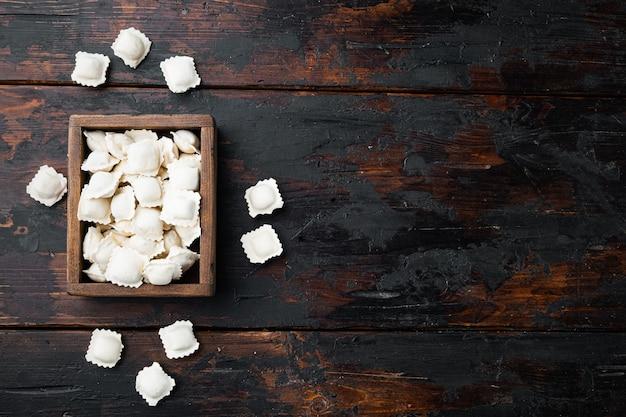 Ravioli congelati impostati in una scatola di legno sul vecchio fondo di tavola in legno scuro, vista dall'alto laici,