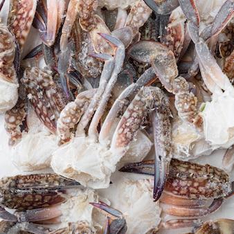 Parti congelate del granchio blu crudo di nuoto messe, su fondo bianco, laici piana di vista superiore