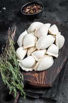 Pierogi gnocchi crudi congelati con patate su una tavola di legno. vista dall'alto.