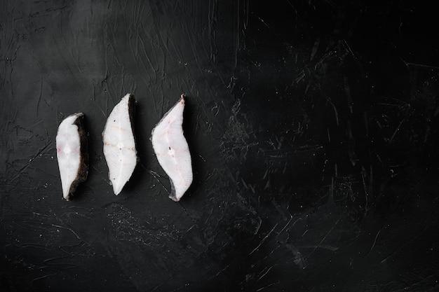 Set di bistecche di pesce crudo congelato, su sfondo di tavolo in pietra nera scura, vista dall'alto piatta, con spazio di copia per il testo