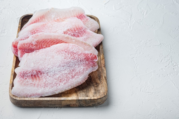 Carne di pesce tilapia cruda congelata, sul tavolo bianco