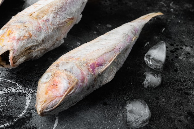 Triglia di scoglio congelata o pesce crudo di barabulka, su sfondo di tavolo in pietra nera