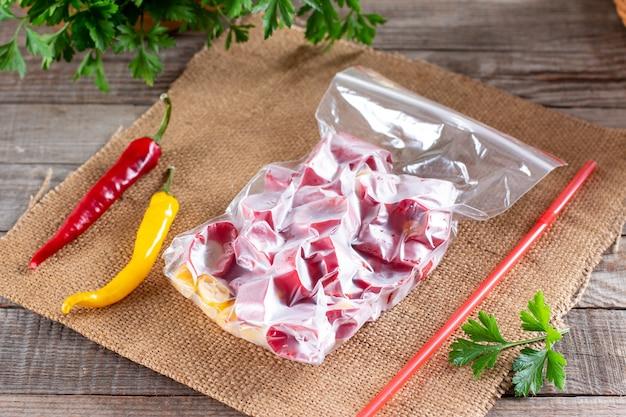 Peperoni rossi surgelati. peperoncino congelato su una tavola di legno sul tavolo. cibo surgelato. verdure surgelate.