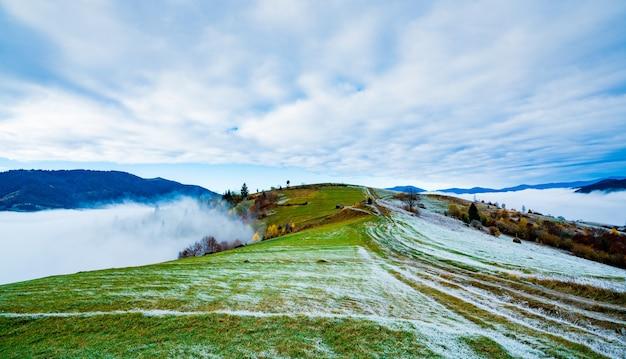 Strada ghiacciata ricoperta di brina bianca sullo sfondo di un bel cielo azzurro e soffice nebbia bianca