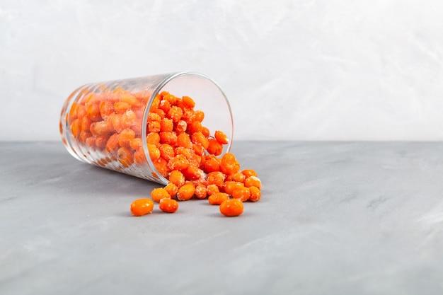Le bacche congelate dell'olivello spinoso si sono rovesciate dal vetro sullo spazio della copia del fuoco selettivo della tavola