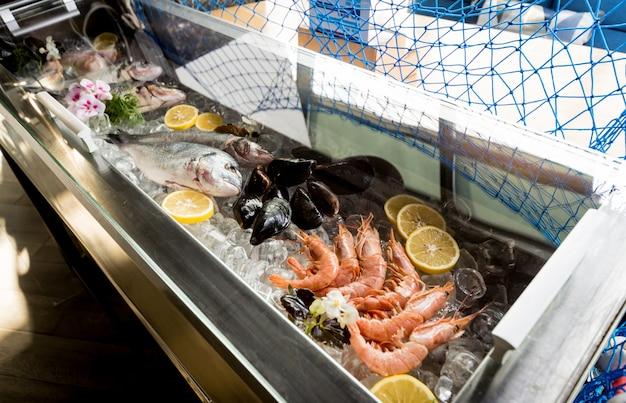 Congelato vedere cibo sul ghiaccio. gamberetti, pesci e conchiglie.