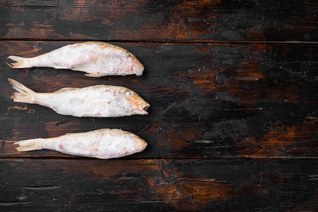 Insieme di pesce congelato di surmulet, su vecchio sfondo di tavolo in legno scuro, vista dall'alto piatta, con spazio di copia per il testo
